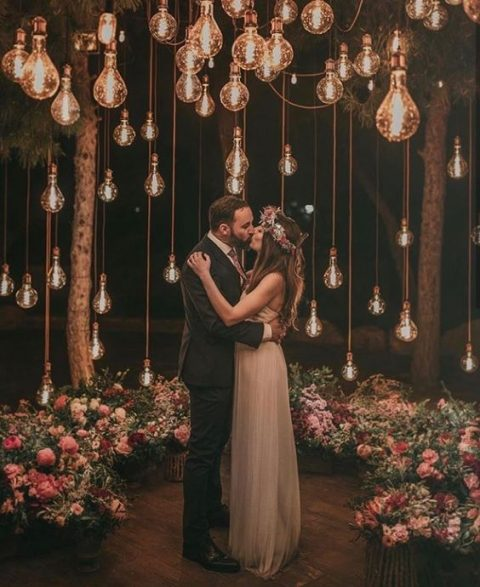 a beautiful wedding ceremony space done with lush blooms and bulbs hanging all over