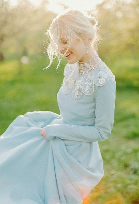 a blue wedding dress with an embellished neckline that features folksy motifs and long sleeves