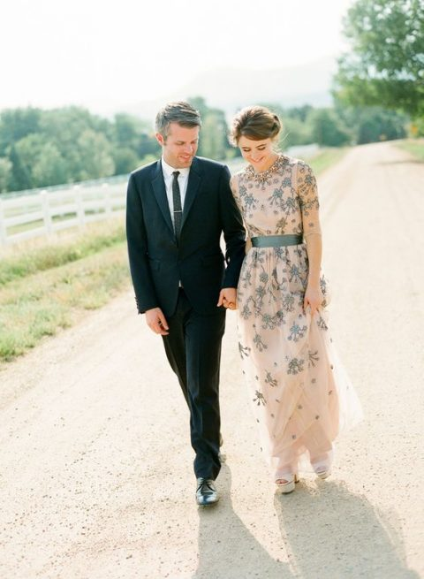 a blush A-line wedding gown with long sleeves and floral embroidery in dark green