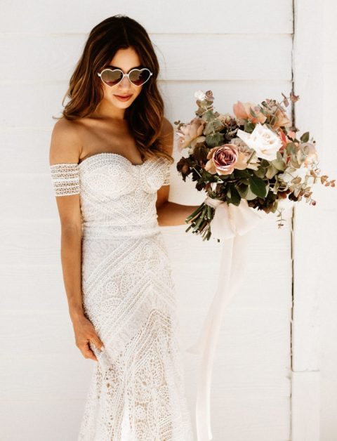 a boho lace sheath off the shoulder wedding dress with straps on the arms by Rue De Seine