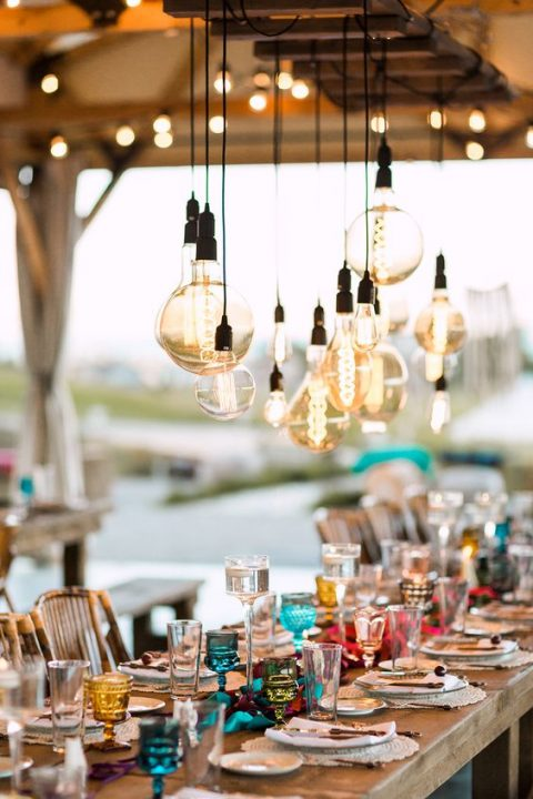 a boho tablescape with bulbs of different sizes hanging over it for more light and an industrial feel