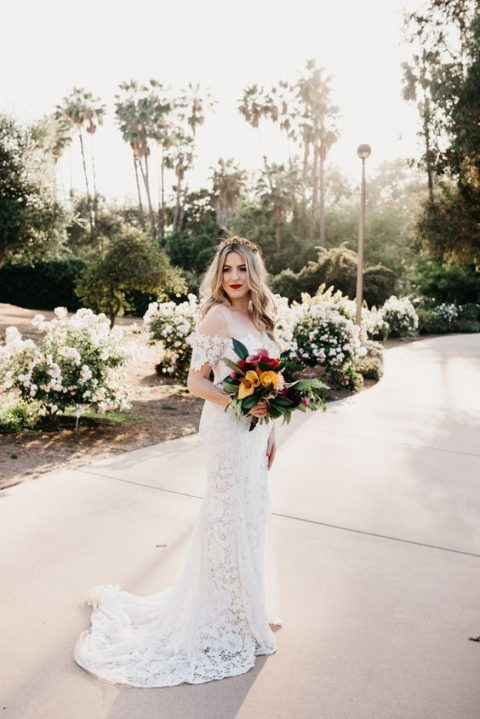 a chic boho lace fitting wedding dress with a train