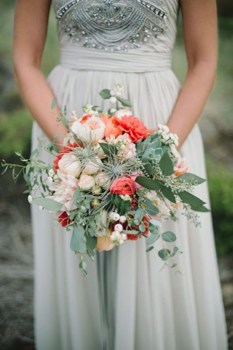 a chic bridal bouquet in cream and coral and with pale greenery