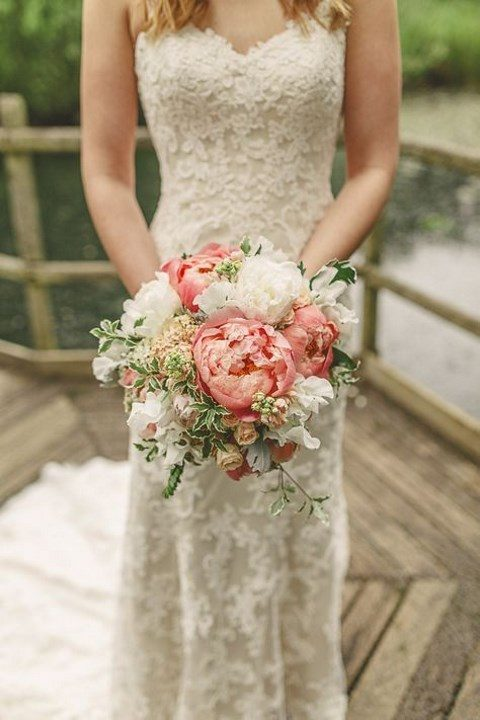 a chic wedding bouquet with white and coral blooms and foliage