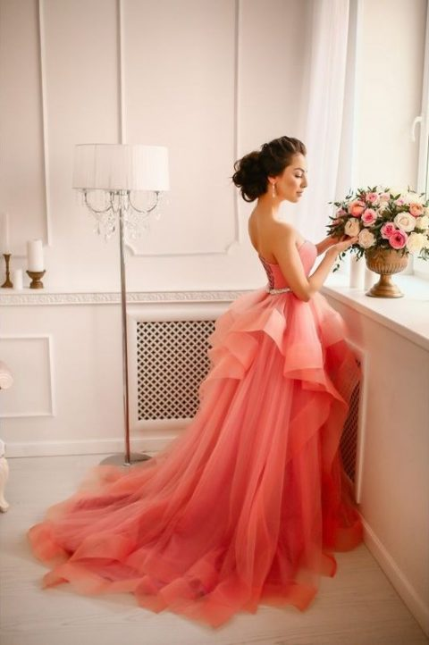 a coral ballgown with an embellished belt and a layered skirt with a train