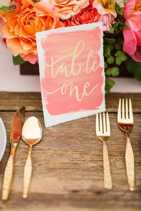 a coral brushstroke wedding card with gold calligraphy