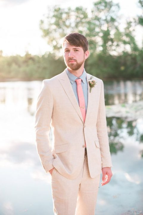 a cremay suit, a light blue shirt, a coral tie and a floral boutonniere