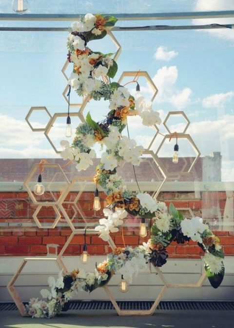 a geometric backdrop of wooden hexagons, bulbs and lush greenery and blooms