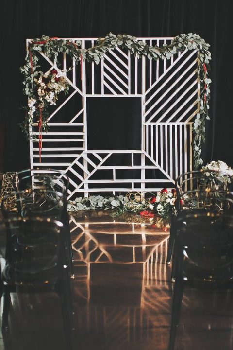 a geometric wedding backdrop decorated with lush greenery and red and white blooms