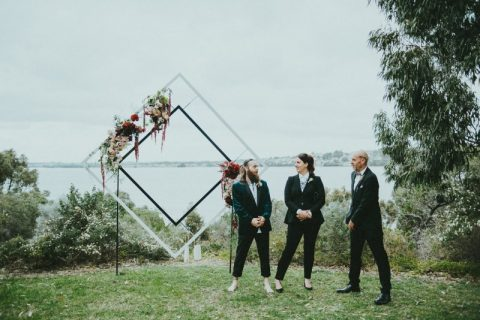 a geometric wedding frame decorated with lush blooms and greenery