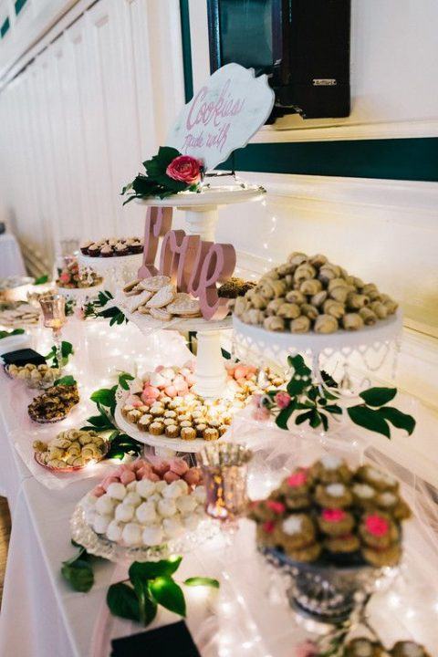 a glam wedding dessert table done with lace and crystal stands and lights