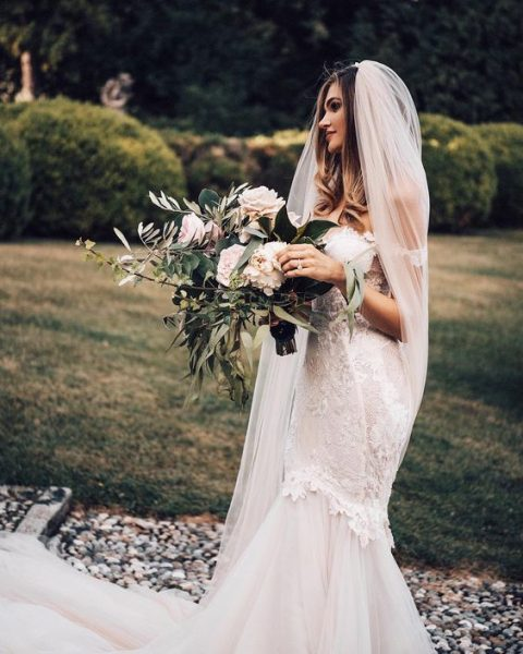 a gorgeous mermaid off the shoulder lace wedding dress and a long veil create a very romantic look