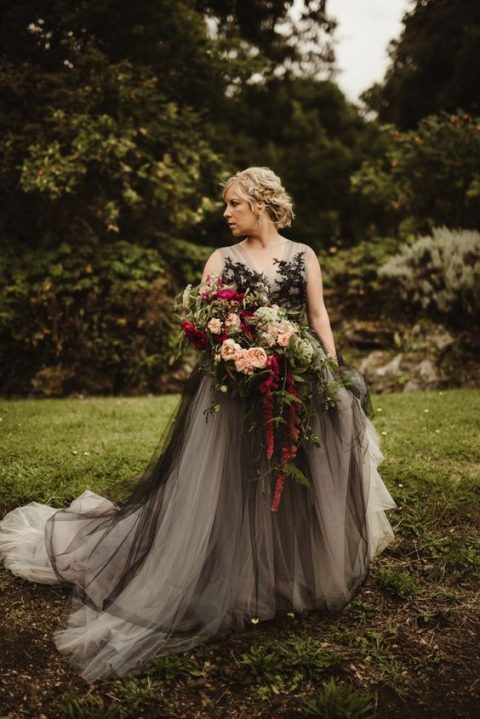 a grey wedding gown with black lace appliques and an A-line skirt with a train for a Halloween bride