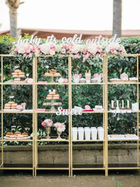 a large dessert table of shelving units and blooms plus cursive letter signs