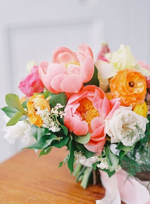 a lush and bright wedding bouquet with white, yellow and coral blooms