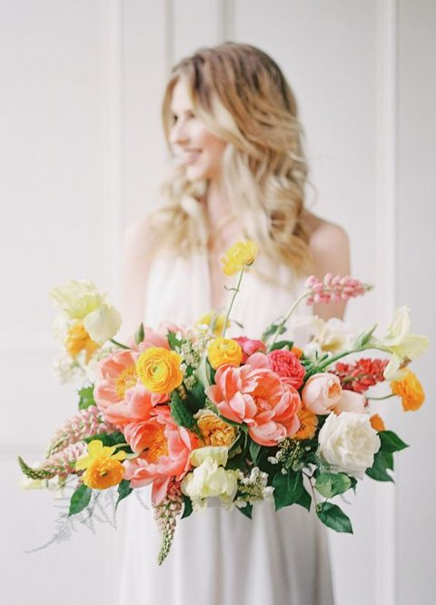 a lush wedding bouquet with white, blush, yellow and coral flowers