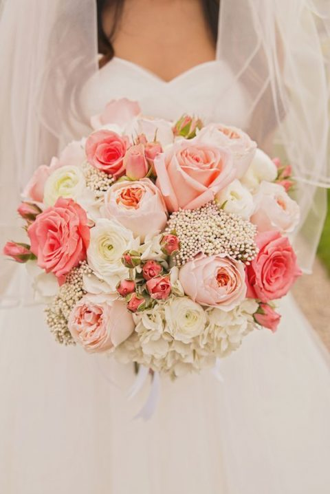 a lush wedding bouquet with white, pink and coral blooms