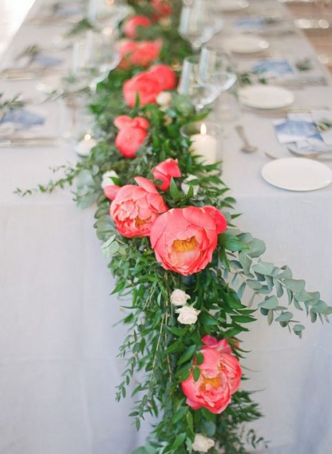 a lush wedding table runner of greenery and coral blooms