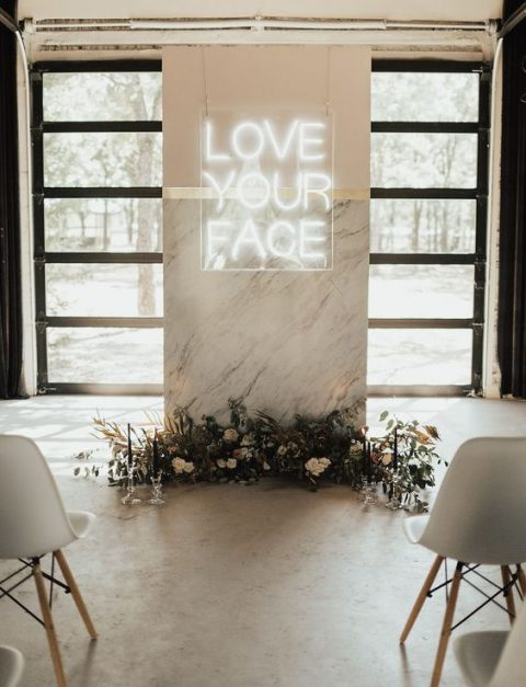 a marble wedding backdrop with a neon sign and blooms and foliage under it