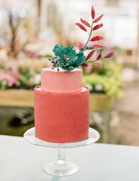 a matte coral wedding cake in two shades topped with a sugar bloom and foliage