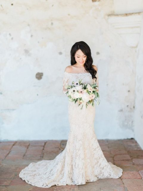 a mermaid off the shoulder lace wedding gown with a train and long sleeves