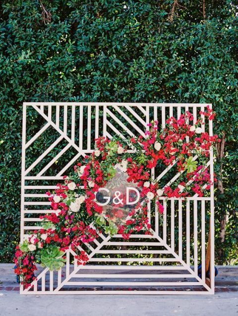 a modern geometric backdrop with a lush red flower cascading garland and monograms