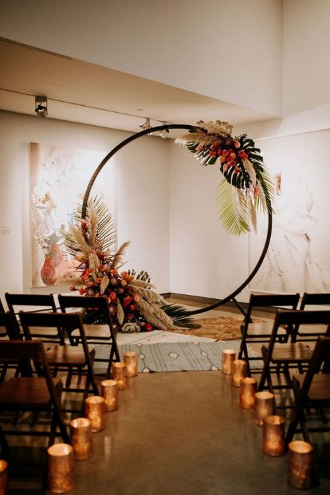 a modern round wedding arch decorated with lush blooms, pampas grass and tropical leaves
