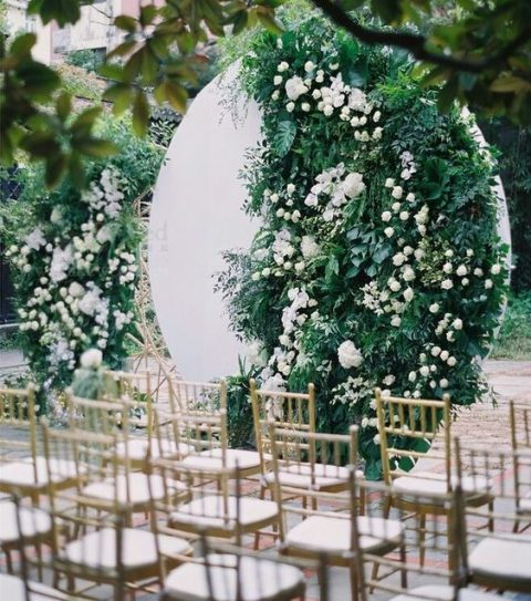 a modern wedding backdrop of a white circle and lush greenery and white blooms