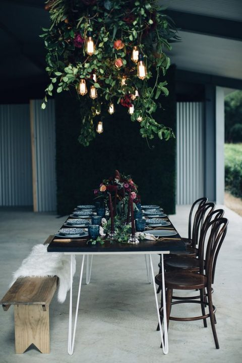 a moody wedding reception with a gorgeous overhead decoration of greenery, dark blooms and bulbs