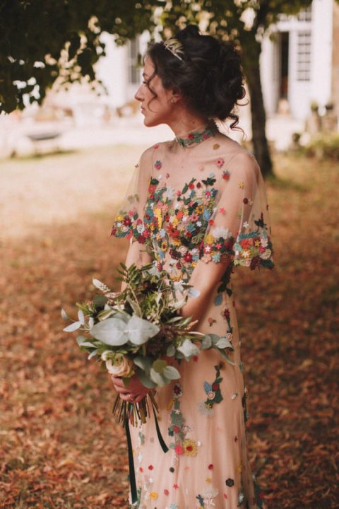 a nude slip dress and a colorful embroidered overdress with wide sleeves and a high neckline