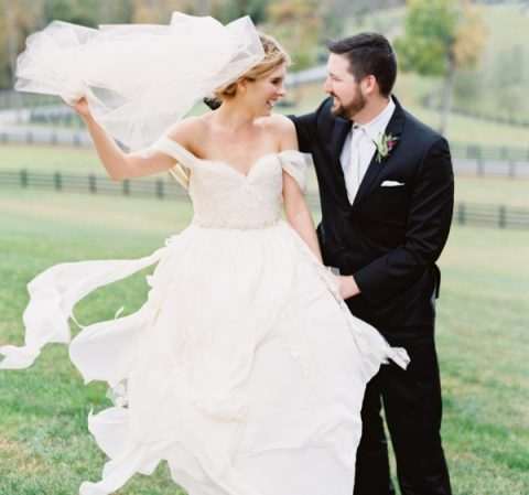 a refined off the shoulder wedding dress with an embellished bodice and a flowy skirt