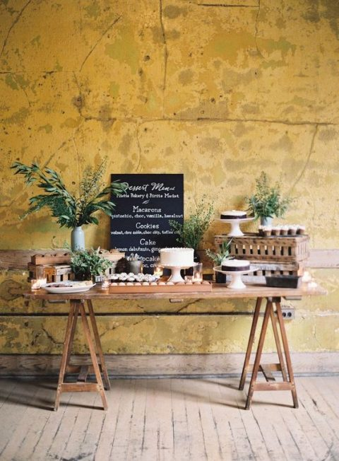 a rustic dessert table with greenery arrangements and a chalkboard sign