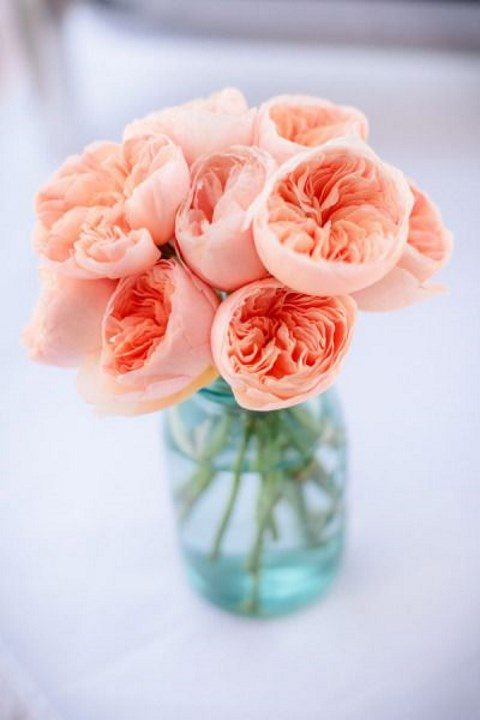 a simple wedding centerpiece of a blue jar and coral peonies looks amazing