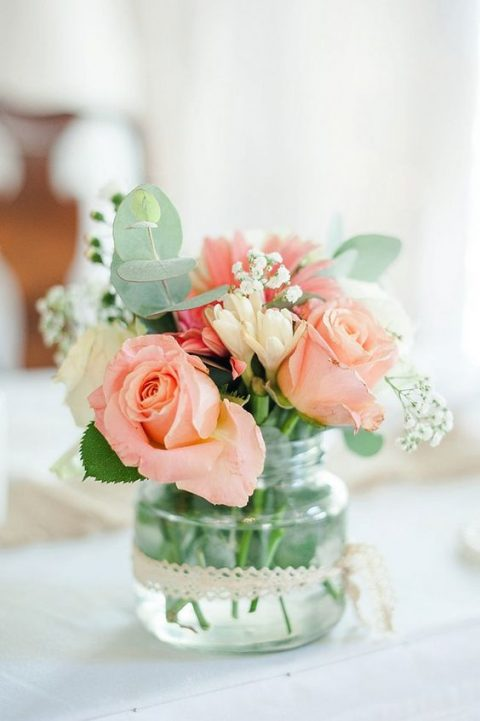 a subtle wedding centerpiece with fresh eucalyptus, baby_s breath, white and coral roses