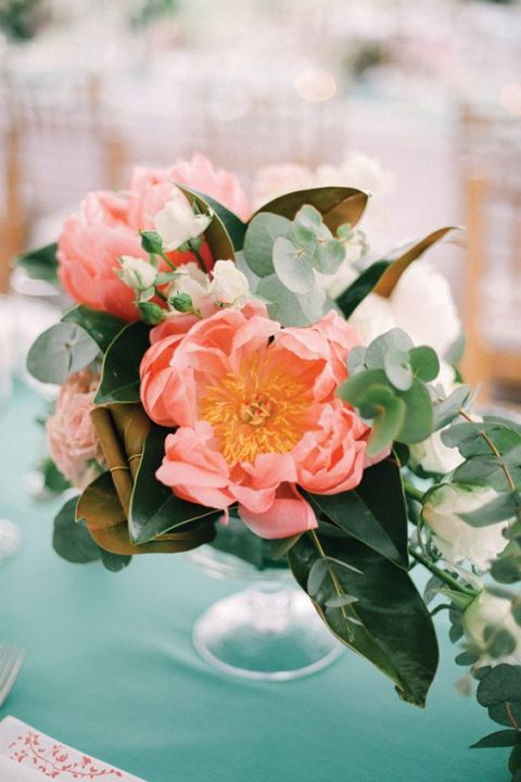 a textural wedding centerpiece with foliage and coral blooms