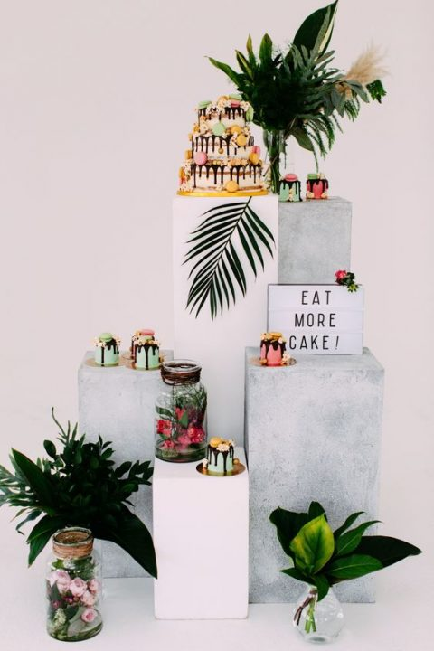 a trendy modern dessert table done with concrete stands and tropical leaves arrangements
