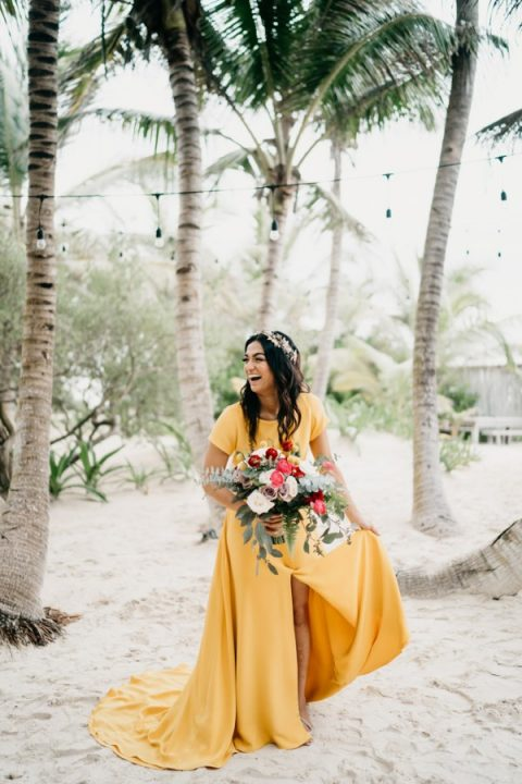 a vibrant yellow wedding dress with a high neckline, short sleeves and a front slit for a tropical bride