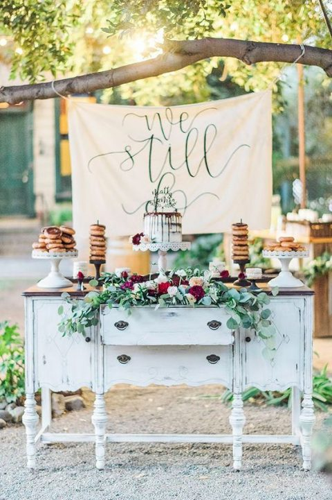 a vintage dessert table with a whitewashed sideboard, lush florals and a sign
