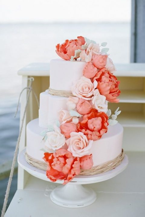 a wedding cake decorated with white and coral sugar flowers