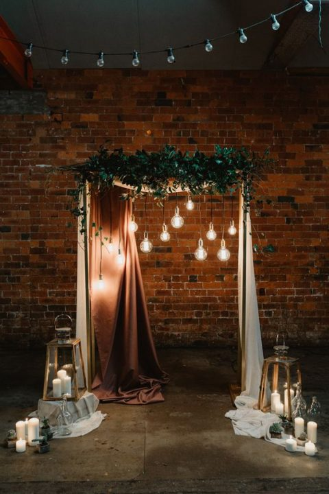 a wedding ceremony arch with fabrics, greenery and bulbs hanging down