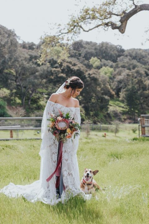an off the shoulder boho lace wedding dress with long sleeves and a train