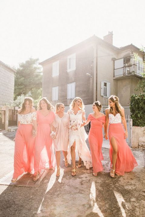 bridesmaids wearing mismatching outfits - coral dresses and floral bodices and coral skirts