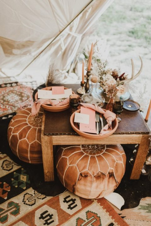 coral napkins and candles accent the wedding sweetheart table ina teepee