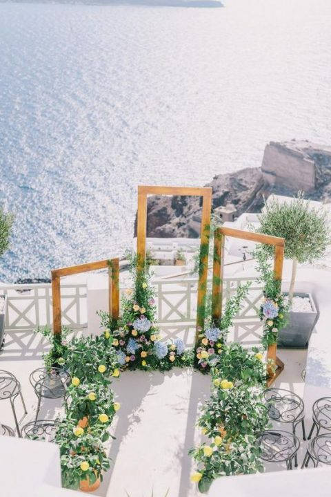 a beautiful Mediterranean wedding ceremony space with several frames and lush blooms and greenery around
