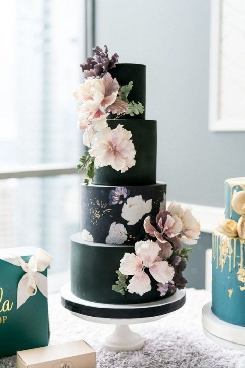 a black floral wedding cake with a painted layer and sugar blooms on the other