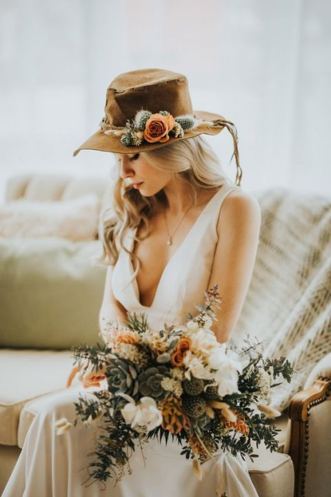 a boho desert bride with a brown hat topped with blooms and thistles