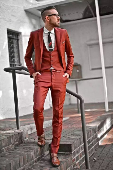 a bold rust-colored three-piece suit, brown shoes and a striped tie