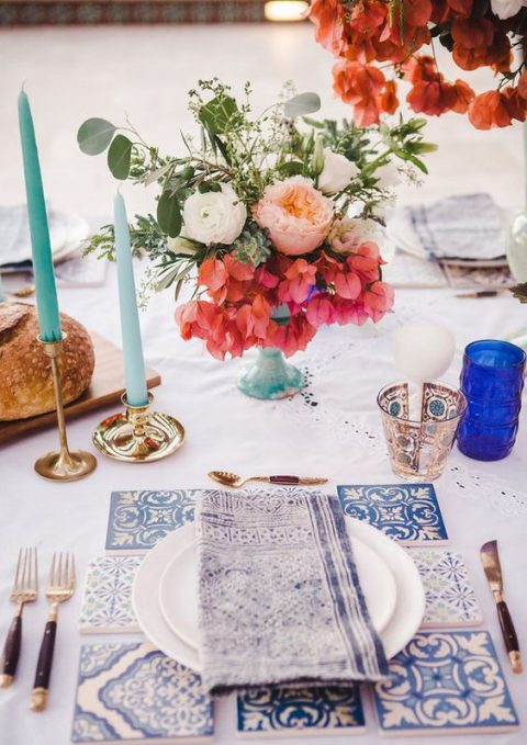 a bright Mediterranean wedding tablescape done with printed blue napkins and candles holders, light blue candles and azulejo tiles