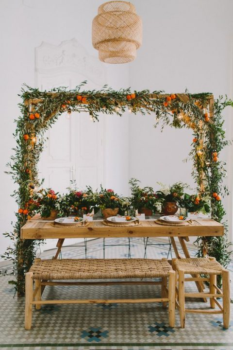 a bright and creative reception space done with potted plants and citrus and an overhead decoration