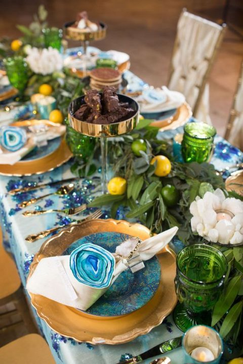 a bright blue and green Mediterranean reception table with candles and citrus table runners